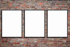 Trois cadres de tableau en blanc sur le mur de briques - maquette encadrée d'affiche avec le fond de mur en pierre images libres de droits