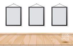 Trois cadres de tableau sur le plancher en bois et le mur blanc Photographie stock libre de droits