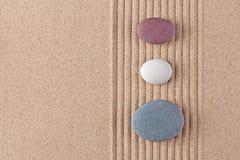 Trois cailloux colorés sur le sable ratissé Image libre de droits