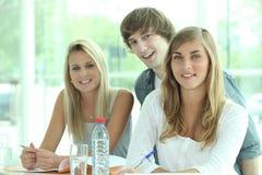 Trois camarades de classe mettant à jour ensemble Images stock
