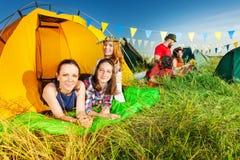 Trois campeurs détendant dans leur tente au terrain de camping Photo libre de droits