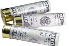 Trois 12 cartouches de fusil de chasse de calibre ont chargé avec cent billets d'un dollar D'isolement sur le fond blanc Image libre de droits