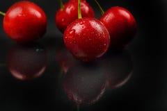 Trois cerises humides rouges sur le fond noir réfléchi dans le St Images libres de droits