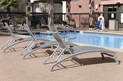 Trois chaises longues reposant le côté de piscine Photo stock