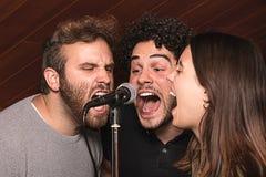 Trois chanteurs chantant avec un microphone avec l'expression euphorique Photographie stock