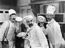 Trois chefs tenant des tartes pour un combat dans la cuisine (toutes les personnes représentées ne sont pas plus long vivantes et images libres de droits