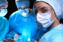 Trois chirurgiens au travail fonctionnant dans le patient chirurgical d'économie de théâtre et regardant le moniteur de la vie Mé Photo stock