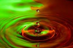 Trois chutes de gouttes dans une eau colorée photos stock