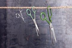 Trois ciseaux s'arrêtant sur une corde Images libres de droits