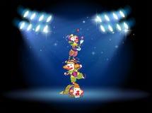 Trois clowns exécutant sur l'étape avec des projecteurs Photo libre de droits