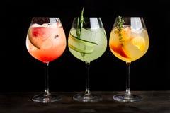 Trois cocktails alcooliques avec les tranches, la glace, les tranches de pastèque et les concombres oranges photos stock