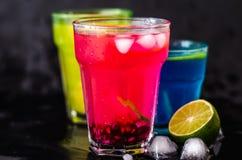 Trois cocktails, chaux et glaces de couleur Photographie stock
