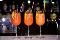 Trois cocktails froids oranges décorés des miettes de sucre, une tranche d'orange et menthe Image stock