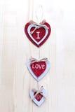 Trois coeurs avec des inscriptions de l'amour sur le fond des conseils n'est pas le fond de la neige, jour du ` s de Valentine Photographie stock