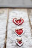 Trois coeurs avec des inscriptions de l'amour sur le fond des conseils n'est pas le fond de la neige, jour du ` s de Valentine Images stock