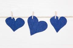 Trois coeurs de denim accrochant sur la ficelle. Images libres de droits