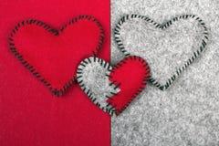Trois coeurs de feutre sur deux milieux différents Photos stock