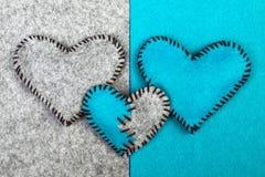 Trois coeurs de feutre sur deux milieux différents Photographie stock