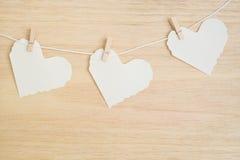 Trois coeurs de papier sur le fond en bois Image stock