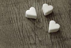 Trois coeurs de sucre blanc sur la table en bois Images stock