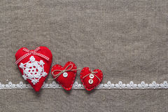 Trois coeurs et dentelles rouges sur le fond de toile de jute Photographie stock libre de droits