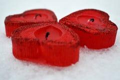 Trois coeurs rouges - bougies sur la neige blanche, un cadeau pour aimé photographie stock