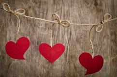 Trois coeurs rouges de tissu accrochant sur la corde à linge photo stock