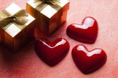 Trois coeurs rouges et deux boîte-cadeau d'or Photographie stock libre de droits