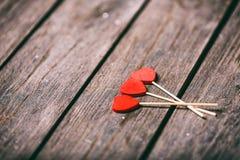 Trois coeurs rouges forment sur le bâton au-dessus du fond en bois Concept de Valentine Foyer sélectif Image libre de droits