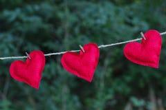 Trois coeurs rouges lumineux accrochant sur la corde à linge dehors Images libres de droits