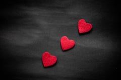 Trois coeurs rouges sur le papier noir Images libres de droits