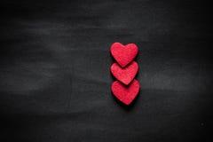 Trois coeurs rouges sur le papier noir Image stock