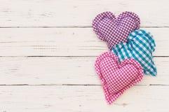Trois coeurs rustiques d'amour sur le bois blanc avec l'espace pour le texte Photographie stock libre de droits