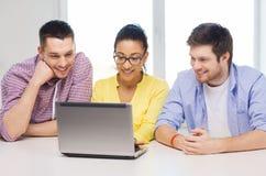 Trois collègues de sourire avec l'ordinateur portable dans le bureau Images libres de droits