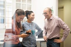 Trois collègues de travail riant dans une cuisine images stock