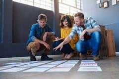 Trois collègues discutant des écritures présentées sur un plancher de bureau photographie stock