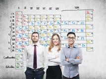 Trois collègues et table périodique Image stock