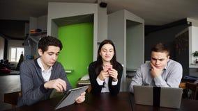 Trois collègues, femelle et deux jeunes hommes s'asseyent dans le réseau social images libres de droits