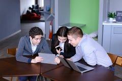 Trois collègues, femelle et deux jeunes hommes s'asseyent dans le réseau social Photos libres de droits