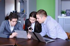Trois collègues, femelle et deux jeunes hommes s'asseyent dans le réseau social Photographie stock