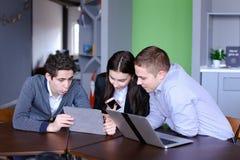 Trois collègues, femelle et deux jeunes hommes s'asseyent dans le réseau social image stock