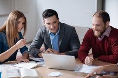 Trois collègues positifs regardant l'ordinateur portable Photo stock