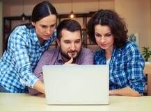 Trois collègues regardant l'ordinateur portable Photo libre de droits