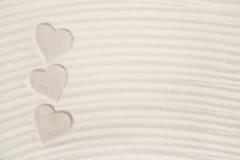 Trois copies de coeur dans le sable pour un fond Photos stock