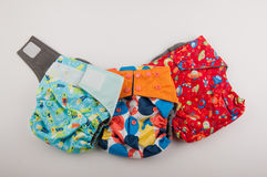 Trois couches-culottes colorées de coton étendues sur le fond blanc Photo stock