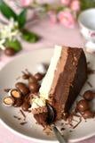 Trois couches du gâteau de crème de chocolat, tranche d'un plat, cuillère prenant un morceau photographie stock libre de droits