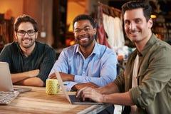 Trois couturiers masculins lors de la réunion utilisant l'ordinateur portable photos libres de droits