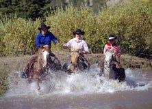 Trois cow-girls croisant l'étang Image libre de droits