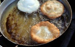 Trois crêpes ont fait cuire dans l'huile de ébullition d'un grand pot photos stock