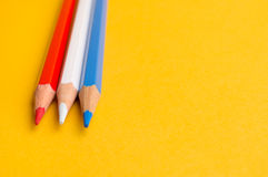 Trois crayons colorés sur le fond jaune Image stock